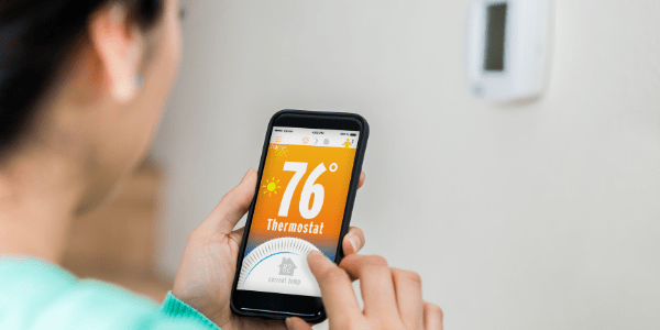 woman pointing at smart thermostat controls on smart phone